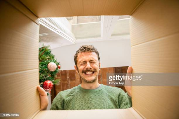 man opening christmas present - gift stock pictures, royalty-free photos & images
