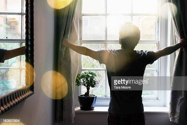 man opening curtains in the morning - luz del sol fotografías e imágenes de stock