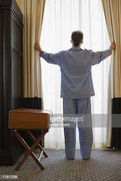 Man opening curtains