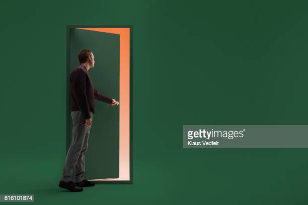 man opening door in futuristic room - deur stockfoto's en -beelden