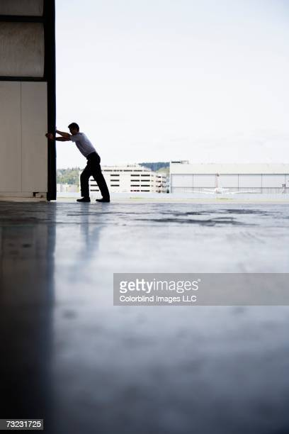 Man opening door to airplane hangar