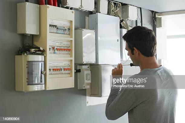 Man opening fuse box, rear view
