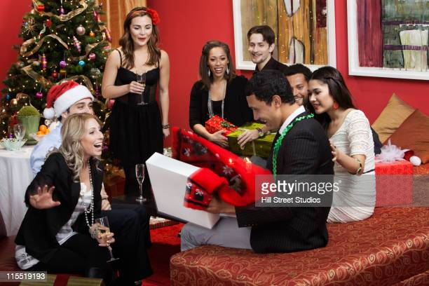 Man opening gift at Christmas party