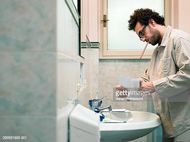 Man opening letter in bathroom, toothbrush in mouth, side view