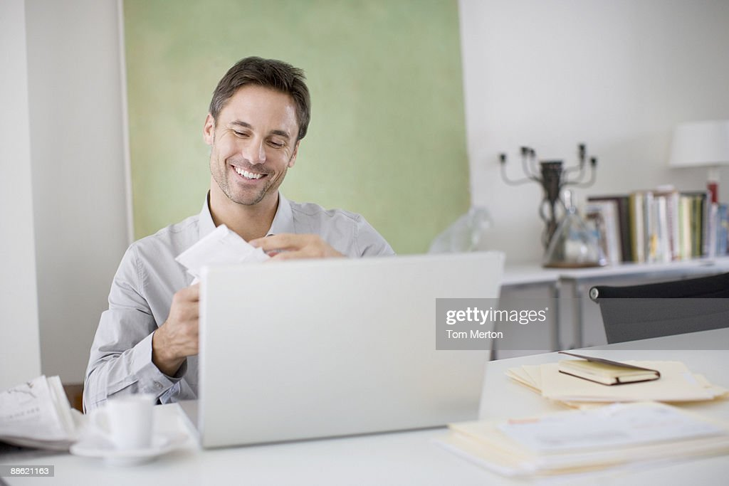Man opening mail at desk : Stock Photo