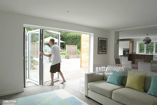Man opening patio doors in living area