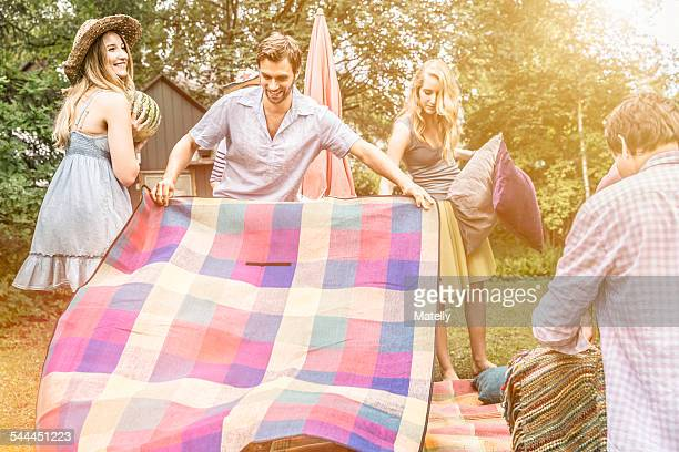 man opening picnic blanket in garden - picnic blanket stock pictures, royalty-free photos & images