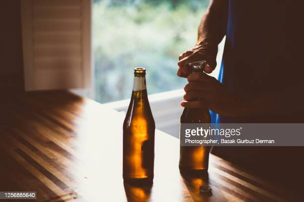 a man opening the cap of the beer bottle with a bottle opener - drink stock pictures, royalty-free photos & images