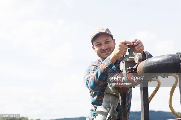 man opening valve on industrial piping, looking at camera smiling - sigrid gombert stock-fotos und bilder
