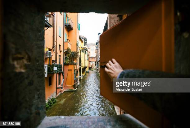 man opening window and looking at the canal in bologna, italy - curiosity stock photos and pictures