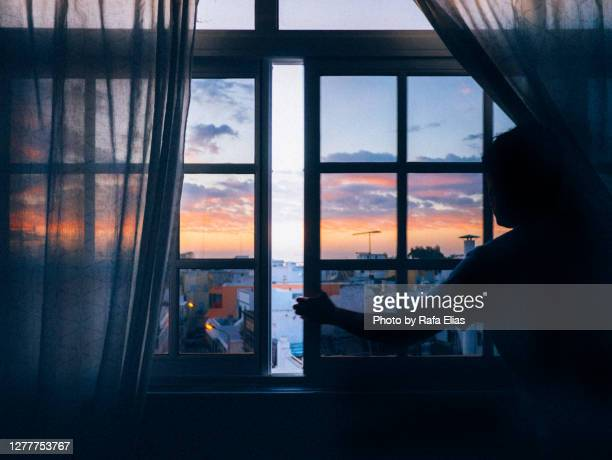 man opening window, old town in the background, dawn time - holy city stock pictures, royalty-free photos & images
