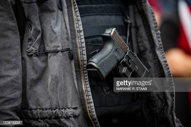 """Man openly carries a handgun during a Proud Boys rally at Delta Park in Portland, Oregon on September 26, 2020. - Far-right group """"Proud Boys""""..."""