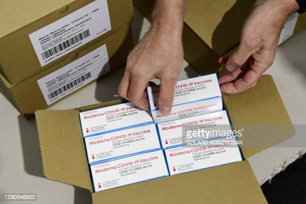 Man opens a a special box containing the first shipment of Moderna's COVID-19 vaccine as 7,200 pieces arrived in Budapest on January 12, 2021. - The...