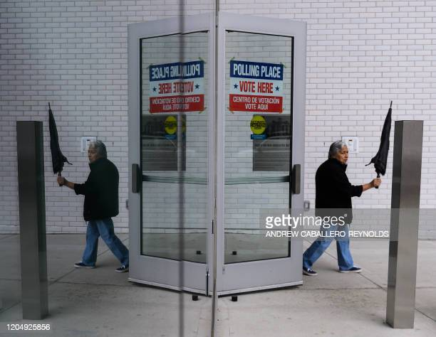 A man opens his umbrealla as he leaves a polling station at the Heights school during Super Tuesday on March 3 2020 in Arlington Virginia Fourteen...