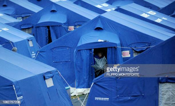 "Man opens his umbrella in a tent camp in L'Aquila on April 28, 2009. Pope Benedict XVI on Tuesday called for a ""rebirth"" of central Italy's Abruzzo..."
