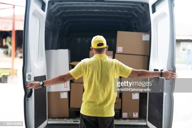 man opens rear doors of delivery van - transportation occupation stock pictures, royalty-free photos & images