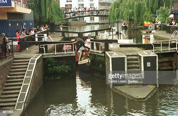 A man opens the lock gates in allowing boats to continue their journey through the Regents Canal July 30 2000 in Camden Lock London When the canal...