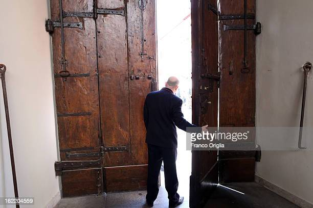 A man opens the main door of the Apostolic Palace of Castelgandolfo on February 20 2013 in Rome Italy The Apostolic Palace and The Pontifical Villas...