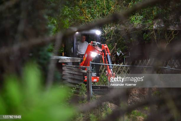Man operates a digger behind fencing at an allotment as police continue to search the area in relation to the disappearance of Madeleine McCann on...