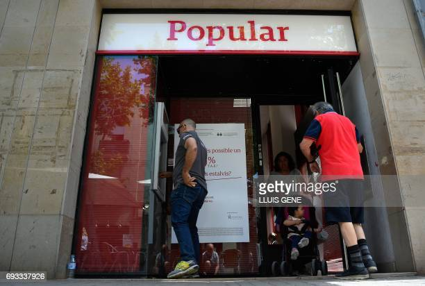 A man operates at the ATM as customers exit a Banco Popular branch on June 7 2017 in Vilanova i la Geltru near Barcelona after European authorities...