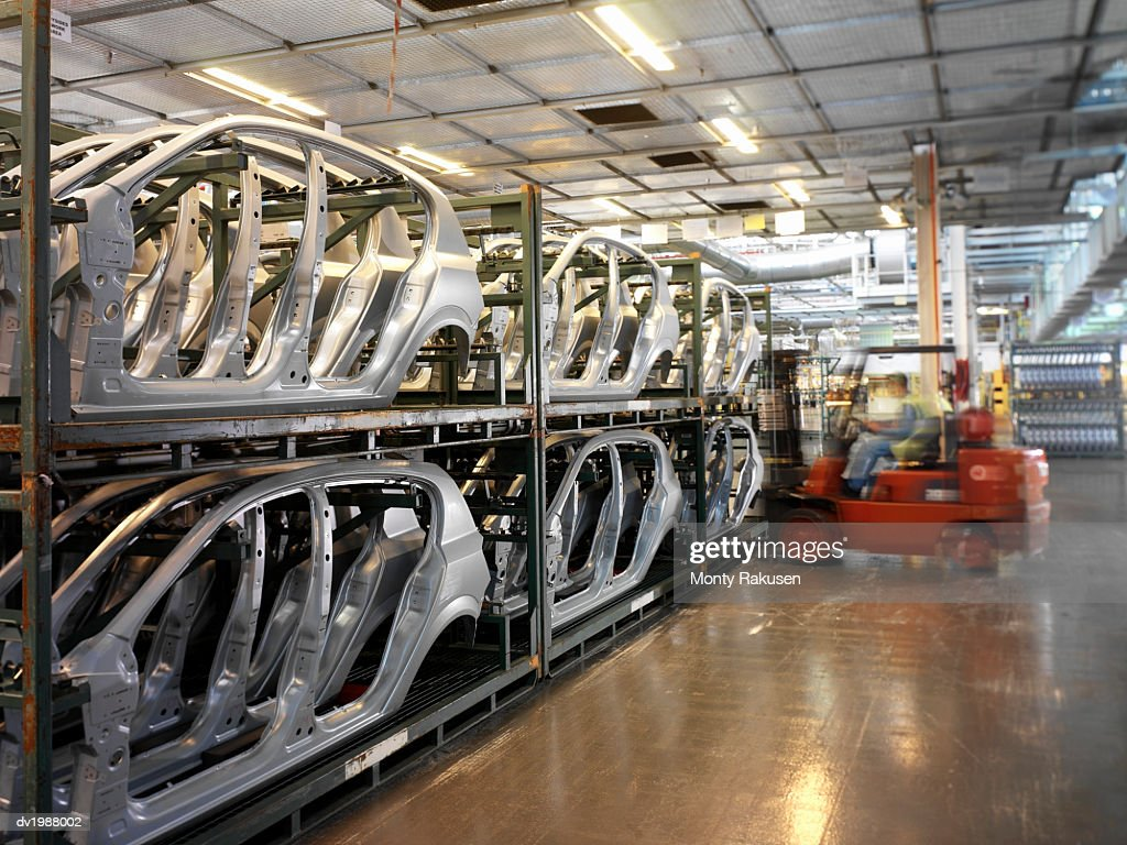 Man Operating a Forklift in a Warehouse Full of Car Parts : Stock Photo