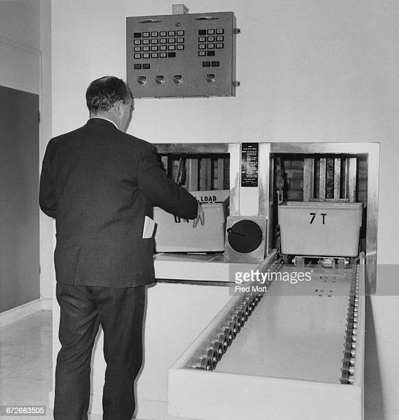 A man operating a horizontal selective conveyor belt system at the New Scotland Yard building on Broadway Victoria London 9th February 1967 The...