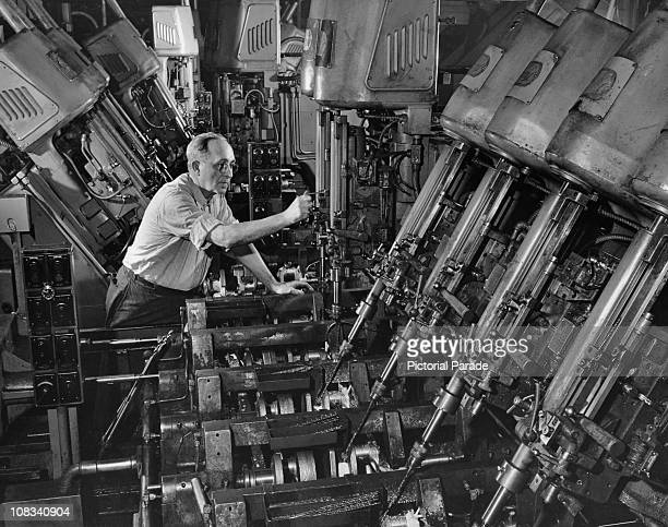 A man operating a machine designed to drill the oil duct system into car crankshafts in a single operation at the Ford Motor Company's Rouge Plant in...