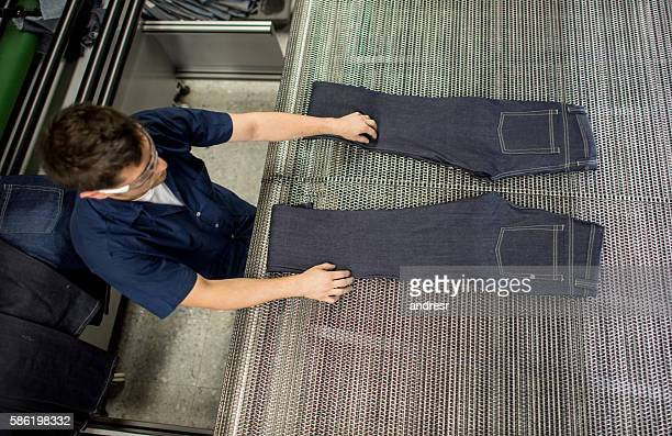 Man operating a ripping jeans machine