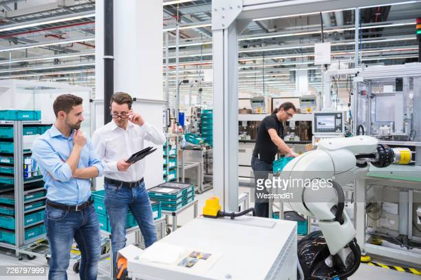 Man operating assembly robot in factory and two men talking