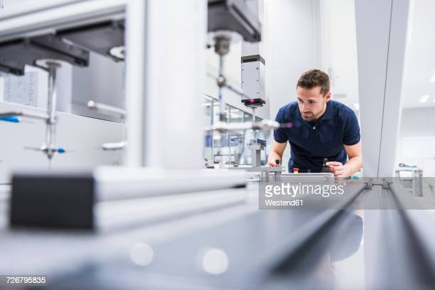 man operating machine in testing instrument room - differential focus stock pictures, royalty-free photos & images