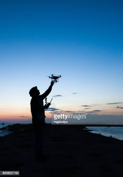man operating of flying drone quadrocopter at sunset - remote control helicopter stock photos and pictures