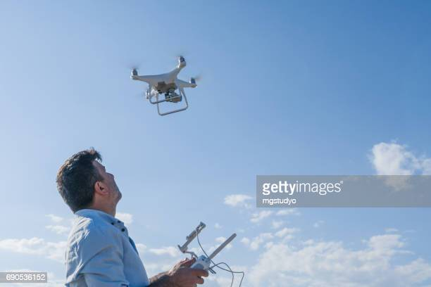 Man operating of flying drone quadrocopter