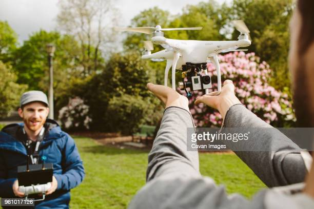 man operating quadcopter while friend holding it in park - remote control helicopter stock photos and pictures