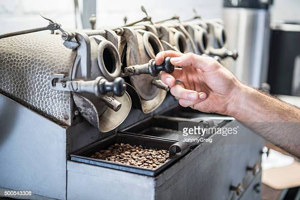 Man operating specialist equipment in coffee roasting warehouse with beans