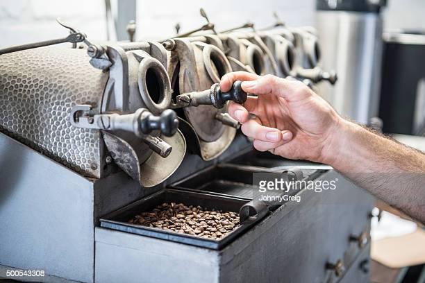 Man 使用専門の機器にコーヒー豆を焙煎倉庫