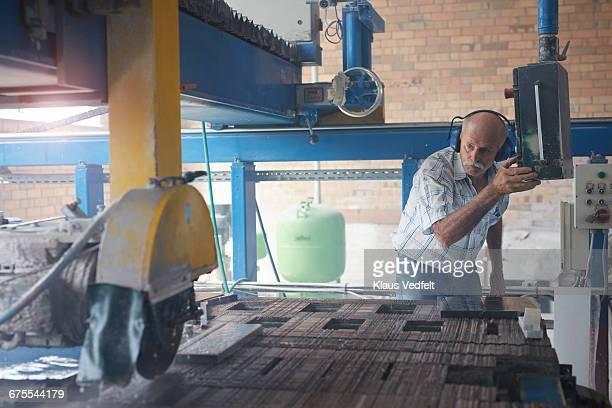 man operating stone cutting machine