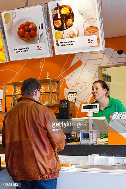 man ordering coffee at counter in dutch hema department store - deventer stock photos and pictures