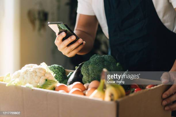man ordering fresh food delivery with mobile phone - mobile app stock pictures, royalty-free photos & images