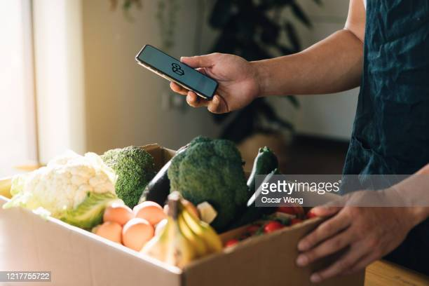 man ordering fresh food delivery with mobile phone - food stock pictures, royalty-free photos & images