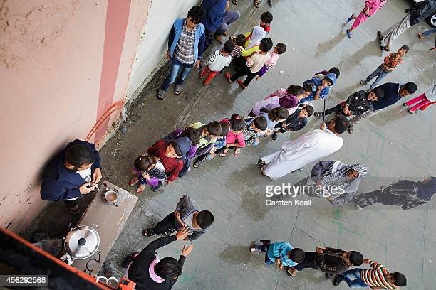 A man orders children to remain in a line to wait for tea in a corner of a refugee camp after crossing from Syria into Turkey in Suruc September 28...