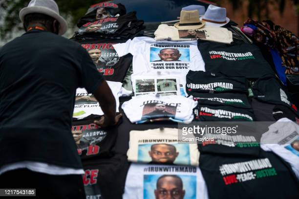 A man organizes Tshirts memorializing George Floyd and Ahmaud Arbery outside the Glynn County Courthouse where Gregory and Travis McMichael attended...