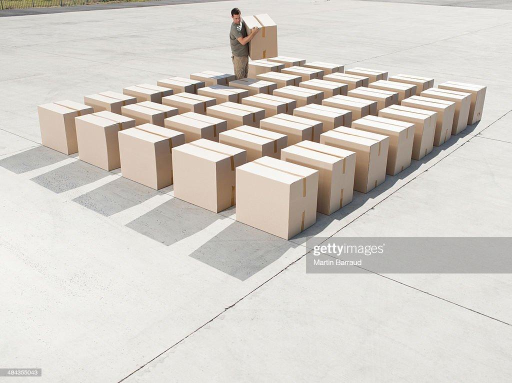Man organizing boxes outdoors : Stock Photo