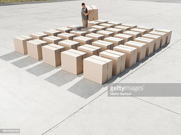 man organizing boxes outdoors - carton stock photos and pictures