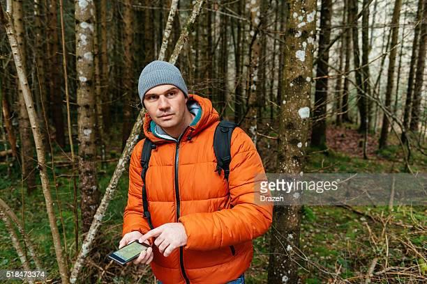 Mann Orientierungslauf in Holz im Winter und Blick auf GPS