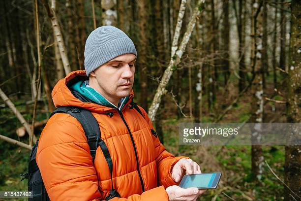 Mann orienteering in Holz im winter und Blick auf Karte