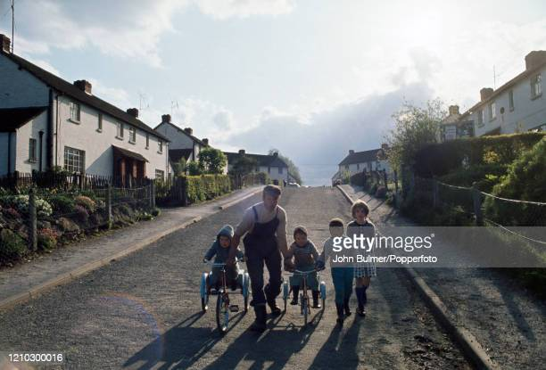 Man out for a walk with four young children, two on tricycles, on the main street, lined with houses on both sides, at Pembridge in England, circa...