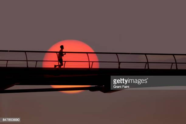man out for morning run over bridge. - dawn stock pictures, royalty-free photos & images