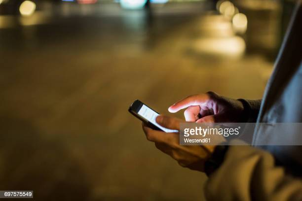 Man outdoors at night using cell phone