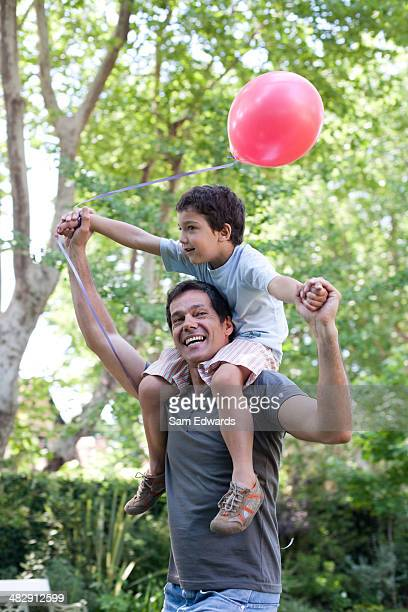 Man outdoors giving smiling young boy shoulder ride with balloon