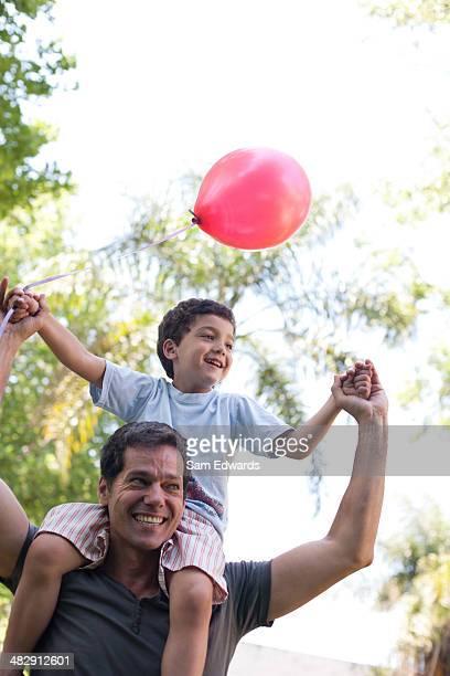 Uomo all'aperto offre sorridente giovane ragazzo con spalla a palloncino